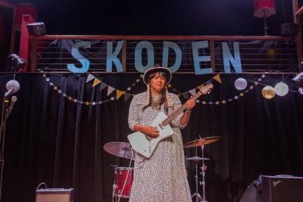 "Female guitarist on stage, ""Skoden"" banner in background"