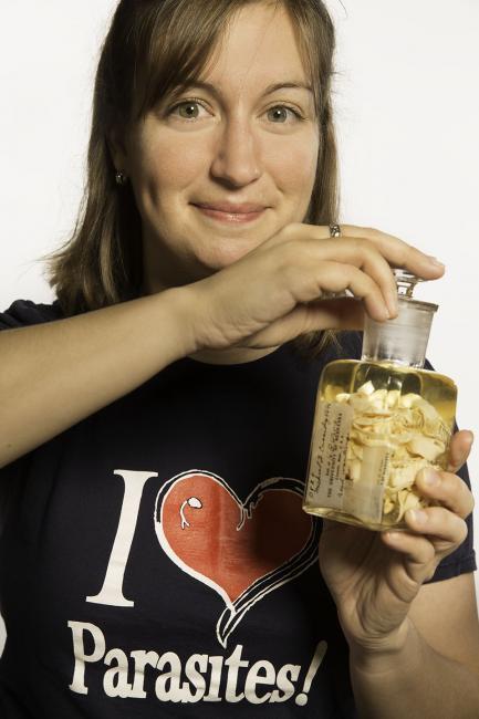 Woman holding specimen jar and smiling