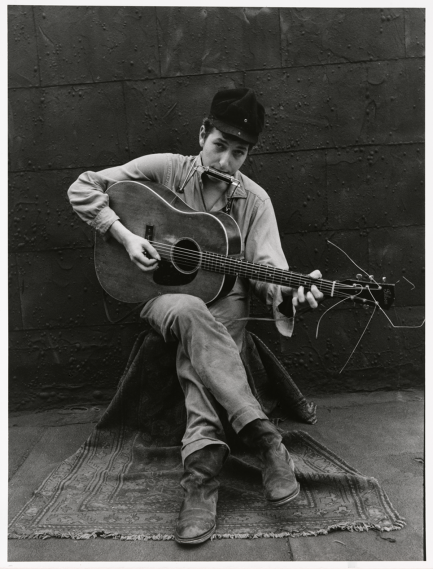 Black and white photo of young Dylan with harmonica and guitar