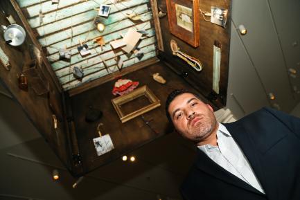 Artist standing beneath his installation