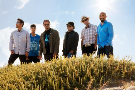 Ozomatli band standing in green field