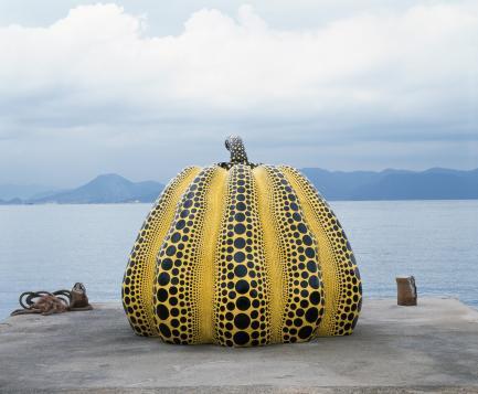 Sculpture of giant pumpkin sitting on pier