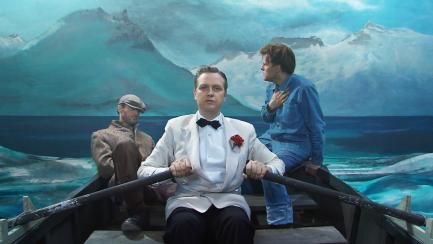 Still image showing man in dinner jacket rowing a boat