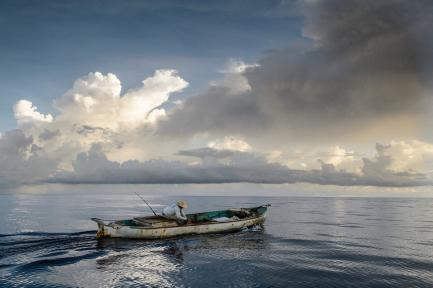 Lone fisherman in small boat against dramatic sky