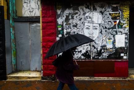 Person on city street with black umbrella