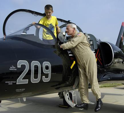 Dailey with child in jet cockpit