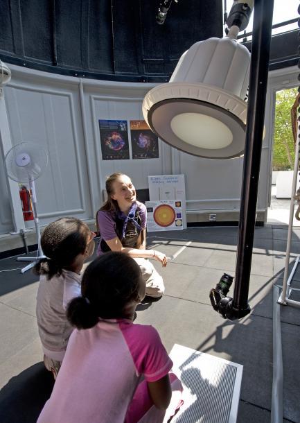 Children listen as woman explains telescope