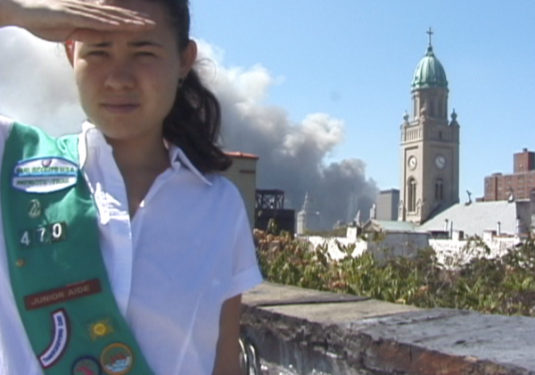Laurel Nakadate, dressed in a Girl Scout uniform, salutes the camera. Behind her is a column of smoke left by the Twin Towers