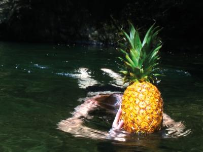 woman swimming with pineapple