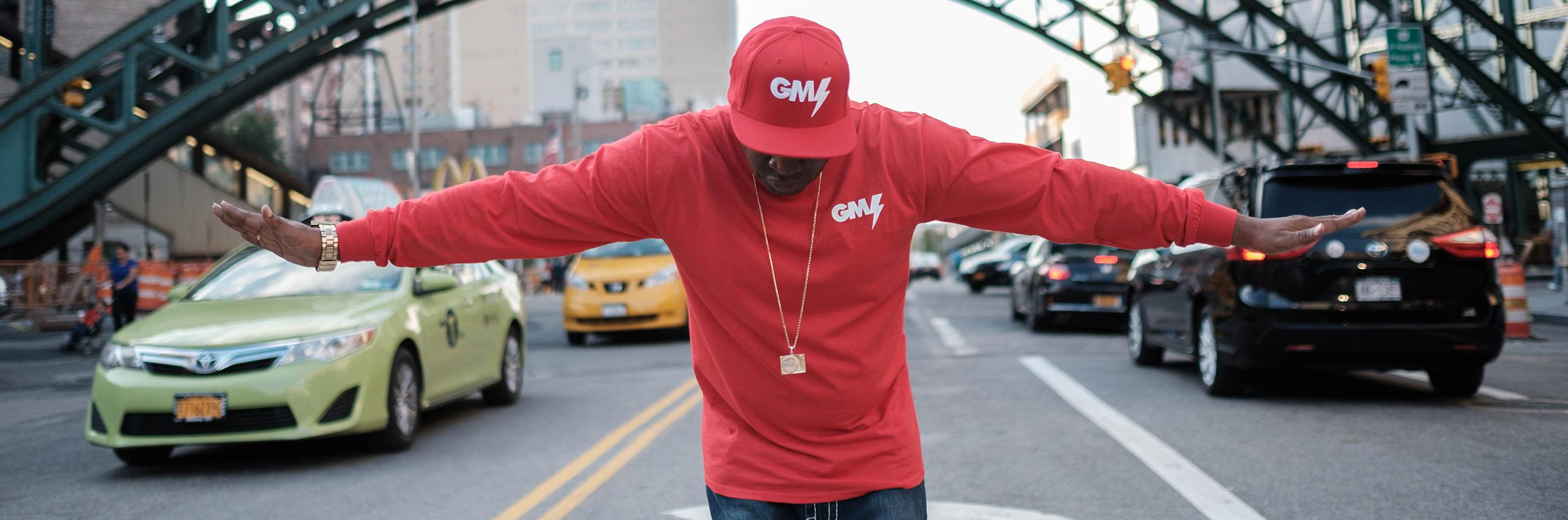 Grand Master Flash in red t shirt and cap with arms outstretched to the side and head bowed.