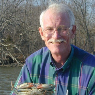 portrait of Hines holding a blue crab