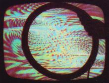 Groovy color patterns on a monitor with a magnetic disk distorting the video image